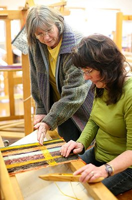 Pam Howard shows a student how to use the loom in the Weaving Studio
