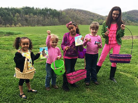 A group of victorious girls show off their bounty from this year's Egg Hunt
