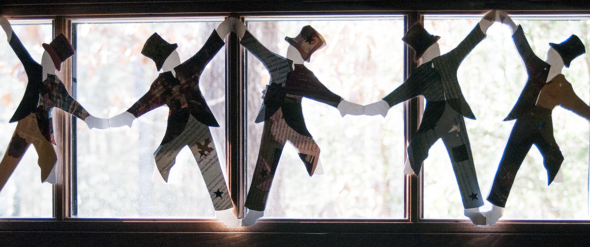 Dapper dandy dancers line the windows of the Community Room.