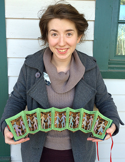 Sara holds the contra dance themed accordion book she made in Annie Cicale's class.