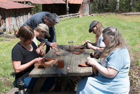 """Students enjoy the nice weather and work on their shoes outside in """"Internal Stitchdown Shoemaking"""" with Michael Ismerio"""