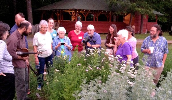A crowd gather to watch the blooming in the Folk School Garden while the Rapper Word Team practices in Open House (behind). Note Charlie's fiddle (left). There is a theory around the Folk School that the primroses like old-time music!