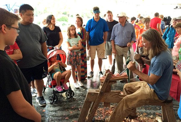 John Campbell demonstrated wood working on the shave horse.