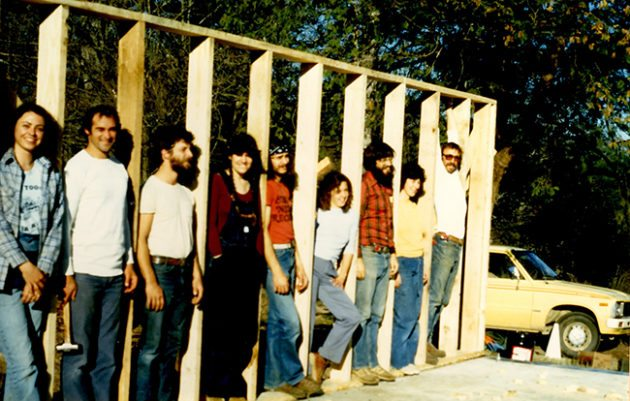 "Participants in the Homesteading Program stand in the wall of Little House, which they built in 1981. (L-R: Toni Meador, ""Jim"" Andy Ward, Nanette Buchen, Michael Thornton, Kim Box, Mike Oliphant, ""Anita,"" Gerard Archibald."