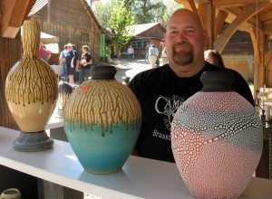 Mike Lalone stands behind his pottery