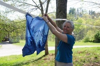 Lillian is very happy on how her white silk shirt turned out when she put it in the blue dye.