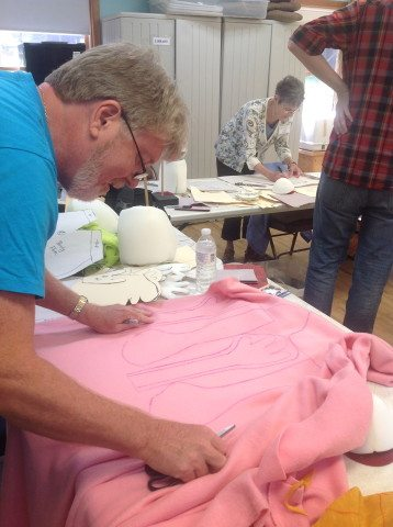 Jens begins cutting fabric for his pink rabbit.