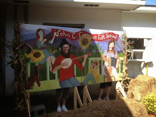 Suzan and friends posing behind the Fall Festival painting at Festival Barn