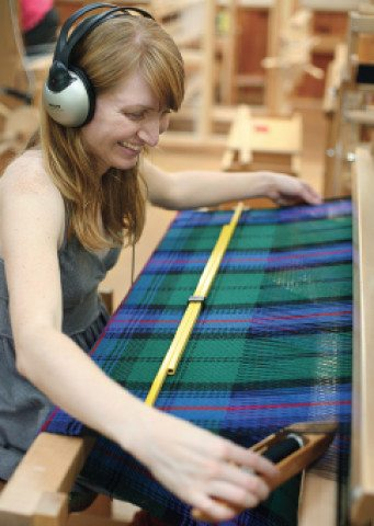 A student weaves a tartan during Scottish Heritage Week.