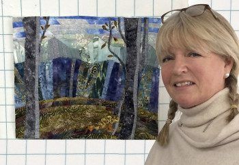 Sissel stands next to her cabin view quilt.