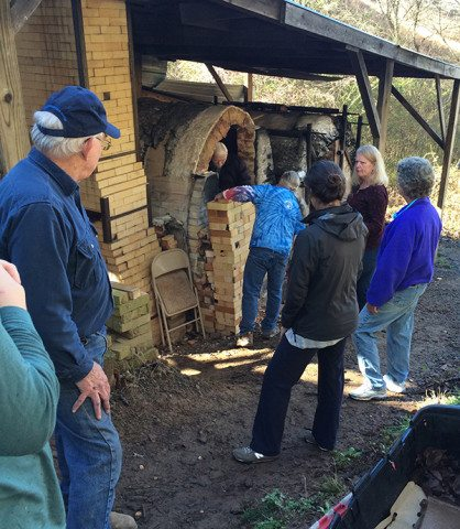 The community helps to unload the kiln, fire brigade-style.