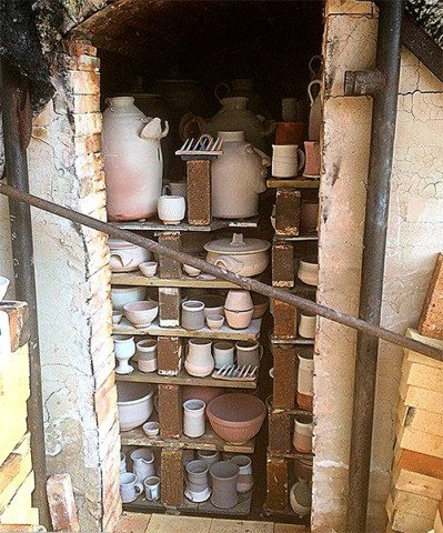 The kiln is loaded with glazed pots.