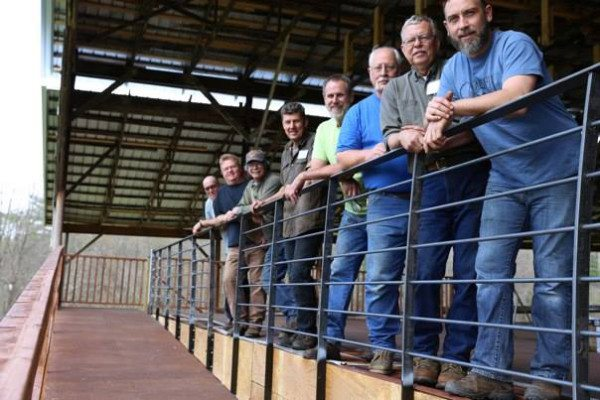 Blacksmith Work Week volunteers stand behind the newly installed Festival Barn Stage railing.