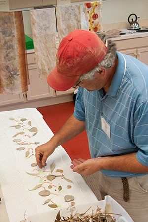 A student places leaves  and bark on the fabric in preparation for the dyeing.