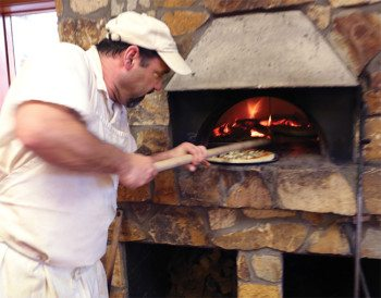 Head Chef, Steve Cipriano puts a pizza in the wood fired oven.
