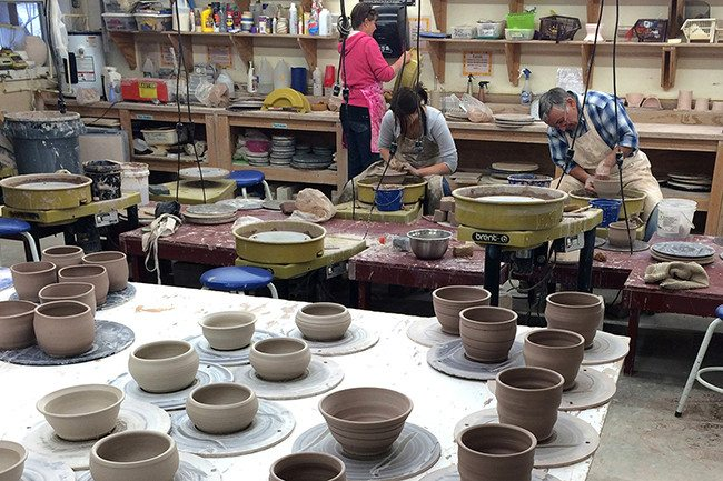 Potters work in the Folk School Clay Studio, donating their time to create bowls for our upcoming fundraising event.