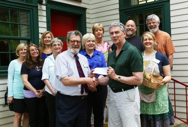 On May 10, 2016, the staff of John C. Campbell Folk School and Empty Bowls volunteers presented a check for $3,188 to Robert Merrill, President of Cherokee County Sharing Center. The Center provides food for over 400 families each month, 30% who are children. Presenting the check, Folk School Director Jan Davidson and Robert Merrill. Also pictured from left to right: Kate Delong, Ellen Sandor, Jennifer Slucher, Dianne Arnold, Marianne Hatchett, Colleen Plonsky, Mike Lalone, Cory Marie Podielski, and Harry Hearne. The Empty Bowls fundraiser for Cherokee and Clay County food banks has been organized by Resident Potter Mike Lalone and hosted by the John C. Campbell Folk School for the past 10 years.